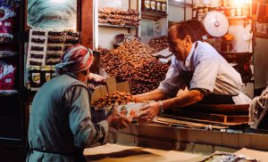 A happy shop owner selling a customer a box full of nuts from his store