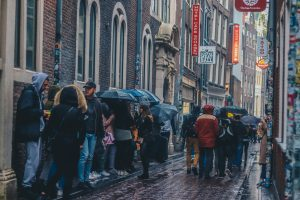 People in coats and with umbrellas queuing down a city street in the rain