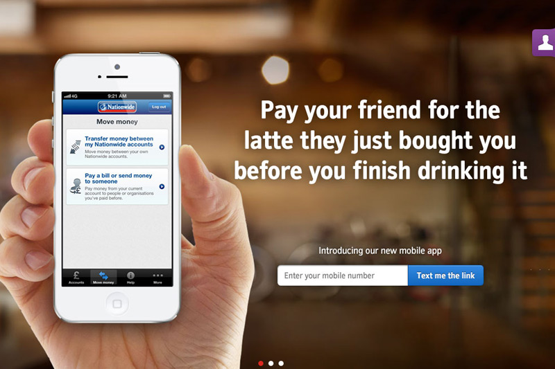 A screenshot from the Nationwide Building Society website showing a mans hand holding an iPhone with the Nationwide website shown on the screen