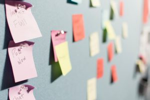 multicoloured post it notes pinned to a pin board wall